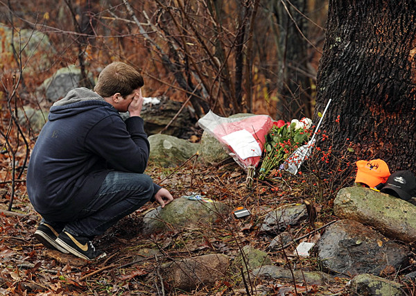 Mackenzie Kelly, 17, twin brother to Katie Kelly, puts a picture of his sister on a flower memorial on Tuesday, November 9, 2010 at the scene along Barnestown Road in Hope where she died along with Daniel Dodge II, 21, of Hope and Misty Leach, 14, of South Thomaston, when the pickup truck they were in crashed into a big tree. (Bangor Daily News/Kevin Bennett)