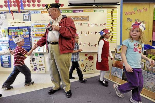 Warren Young, center, of Bradley, a U.S. Army veteran who served in the Korean War, shook hands with five-year-old Landen Roy (cq), left, as he, Jaicee Cline (cq), 5, Annie Roach (cq), 5, Kyiesha Swan (cq), and other classmates in Michelle Morneault's kindergarten class marched around their classroom at Old Town Elementary School. They later joined the entire student body Wednesday afternoon to honor military veterans and active duty personnel who visited the school Wednesday. They sang patriotic music, read poetry and offered thanks to military veterans on the eve of Veterans Day. (Bangor Daily News/John Clarke Russ)