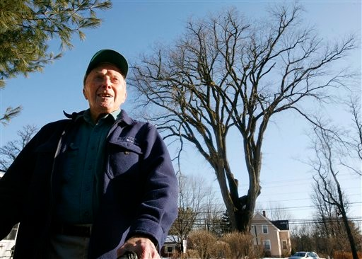 FILE - In this Dec. 14, 2009 file photo, Frank Knight, 101, of Yarmouth, Maine, stands in front of an elm tree known as &quotHerbie&quot in Yarmouth. Knight, who is recently retired, took care of the tree for about 50 years while working as the Yarmouth tree warden.  The tree, estimated to be over 225 years old, was cut down in January. (AP Photo/Steven Senne, File)