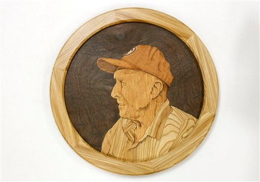 Former tree warden Frank Knight is depicted in a carving made from wood that came from a 217-year-old elm tree that Knight saved from several bouts of Dutch elm disease, Thursday, Nov. 11, 2010, in Yarmouth. Nearly nine months after being cut down, artisans have transformed some of the wood from New England's champion elm tree into a variety of products including an electric guitar. (AP Photo/Robert F. Bukaty)