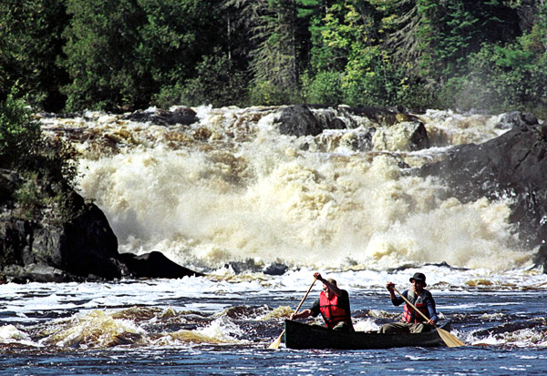 Canoeists Jason Chamberlain, (left) and Andrew Martin, both of Fort Kent, Maine, paddle through whitewater in September 1999 after portaging the 40-foot Allagash Falls (background) on the Allagash Wilderness Waterway in northern Maine. (AP Photo/Robert F. Bukaty, File)