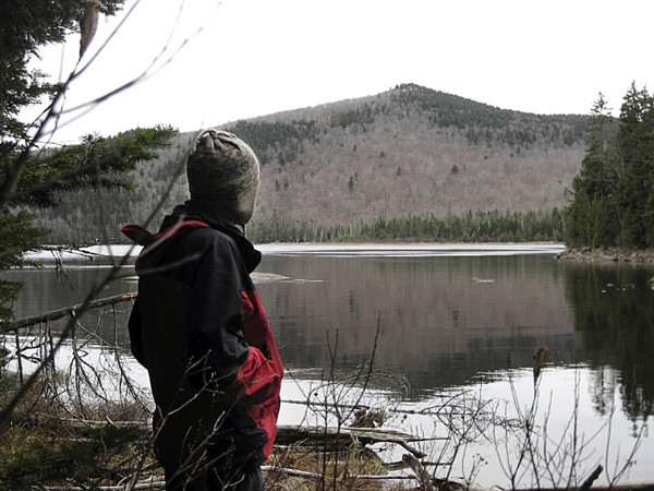 Brad Viles stops on the shore of Big Moose Pond last Sunday to check out the summit of Little Moose Mountain in Greenville.