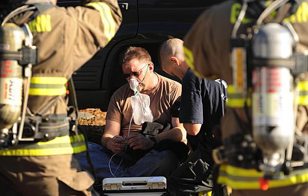 Ellis Stewart sits slumped against a car as firefighters treat him for smoke inhalation after he attempted to put out an automotive garage fire on the Townhouse Road in Levant on Friday, November12, 2010. Stewart was alone in the garage working on a car when it caught fire. The garage is owned by Rick Bushey, who was not at the garage at the time of the fire. (Bangor Daily News/Kevin Bennett)