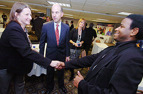 Allen Johnson, right, of Pittsfield,  founder of  wholesomemusic, congratulated Zeomatrix President and CEO Susan MacKay (cq) after MacKay made the winning five-minute business pitch during Wednesday's Innovation to Venture conference at the Black Bear Inn in Orono. Looking on were U.S. Patent and Trademark Office Director David Kappos and Target Technology Incubator director Debbie Neuman (cq).  (Bangor Daily News/John Clarke Russ)