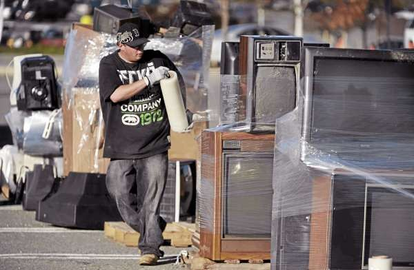 Phil Keller a worker with Ewaste of Auburn shrink wraps old TV's in the Bangor Mall parking lot on Saturday, November 13, 2010. Ewaste hauled off two tractor trailers and one smaller truck  full computers, TV's and related electronic waste. (Bangor Daily News/Kevin Bennett)
