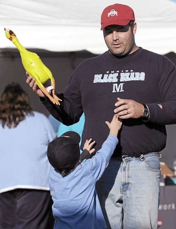 Steve Keib of Glenburn holds a rubber chicken as his son, Evan, begs for the chance to throw it on Saturday, November 13, 2010 during the WHCF and Solution FM Turkey Toss at Lamb's Bible and Book Store in Bangor. People were encouraged to bring a cash donation or a frozen turkey to benefit families in need of Thanksgiving dinners, in exchange for the chance to toss a rubber chicken to win prizes. Manna Ministries will distribute the frozen birds. (Bangor Daily News/Kevin Bennett)