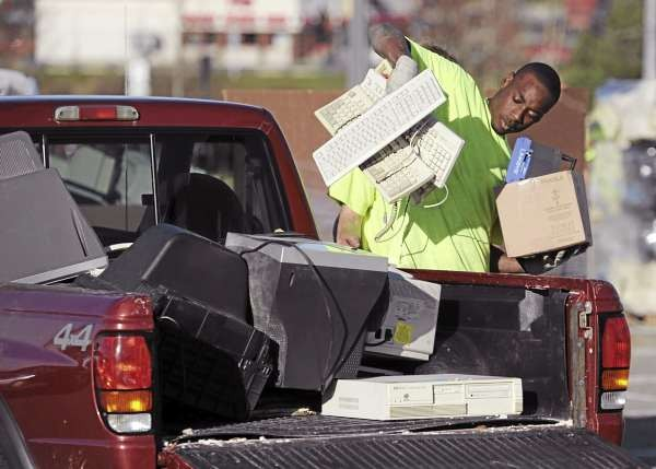 Ikeem James a worker with Ewaste of Auburn unloads used computer equipment from a pickup truck in the Bangor Mall parking lot on Saturday, November 13, 2010. Ewaste hauled off two tractor trailers and one smaller truck  full computers, TV's and related electronic waste. (Bangor Daily News/Kevin Bennett)
