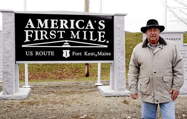 Thousands of visitors to Fort Kent have had thier pictures taken in front of the old wooden sign marking the beginning of US Route 1. On Sunday C.R. Joy of Southington, Conn., became the first to have his photo snapped in front of the new sign following the dedication of American's First Mile. (NEWS photo by Julia Bayly