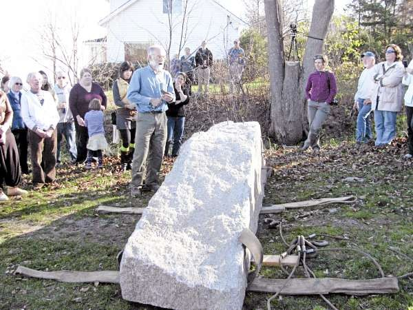 Artist Douglas Coffin stands in front of a 12,000 pound granite block that he split Saturday afternoon using ancient tools at the Allyn Street rangeway in Belfast. The stones will be used to mark the city-owned right-of-way to the bay. (Abigail Curtis/BDN)