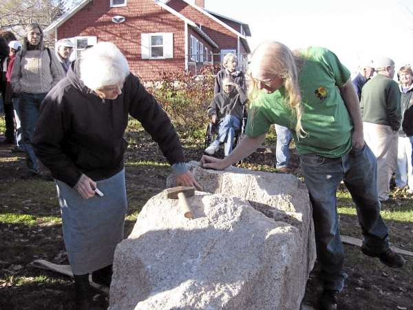 Onlookers gather Saturday afternoon around the granite block that artist Douglas Coffin had split in two using an ancient method called feather-and-wedge at the Allyn Street rangeway in Belfast. The stones will be used to mark the rangeway, a right-of-way to the bay. (Abigail Curtis/BDN)