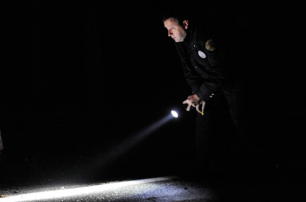 Bangor Police officer James Dearing uses his flashlight to scan the road surface for evidence after a compact car crashed on outer Essex Street in Bangor before 4 p.m. Tuesday, Nov. 16, 2010.  One of the occupants died at the scene and the other occupant was transported to Eastern Maine Medical Center. (Bangor Daily News/John Clarke Russ)