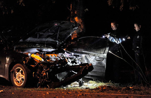 Bangor police officers train their flashlights on the wreckage of a compact car that crashed on outer Essex Street in Bangor before 4 p.m. Tuesday.  One of the occupants died at the scene and the other occupant was transported to Eastern Maine Medical Center.  BANGOR DAILY NEWS PHOTO BY JOHN CLARKE RUSS