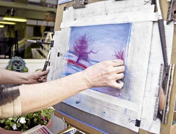 ARTWALKNOV4: Artist Leigh Osgood worked on a landscape painting outside the Bennett Gallery on Central Street during the June 2010 Bangor Artwalk. (Photo courtesy of Liz Grandmaison)