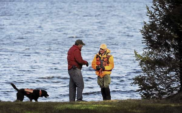 Jay Holweger, right, of Searsport talks with property owner Tom Pierce  before working his dog Maddy along the shore line of Baker Brook Cove on Moosehead Lake in Tomhegan Township on Friday, November 19, 2010. Holweger is part of Maine Search and Rescue Dogs and his dog Maddy is certified in wilderness air scent tracking. The pair were searching for James Russell, who was last seen on Sunday. (Bangor Daily News/Kevin Bennett)