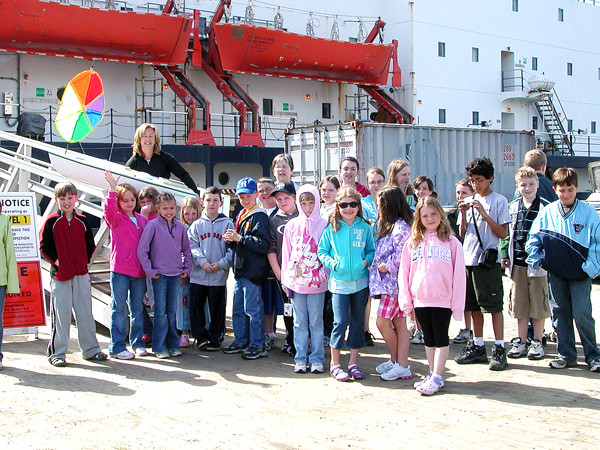 Old Town Elementary School K-Kids stand with group advisers Mary Bagley, left, and Kristi St. Peter, who are holding a four-foot vessel with a GPS the students raised money to purchase. Maine Maritime Academy cadets, aboard the training ship the State of Maine, launched the Old Town K-Kids' boat off the coast of Virginia in June 2009. The small vessel was found inJuly by an Irish farmer. Here the K-Kids are delivering the boat to the State of Maine just before her training voyage May 2009. (Photo courtesy of Old Town Elementary School)