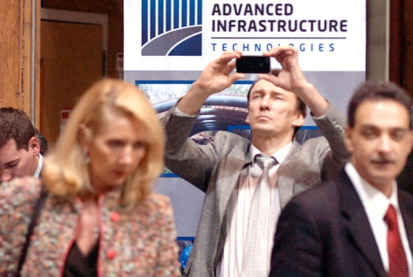 Andrey Andreev, strategic development director with Russian-based Noviy Proekt, takes a photo of bridge components before the start of Friday morning's press conference at the University of Maine's Advanced Structures and Composites Center. Russian and local officials announced a business partnership to implement the university's Bridge-in-a-Backpack technology at the 2014 Winter Olympics in Sochi on the Black Sea. In the foreground are  Advanced Infrastructure Technologies board member Elita Kane, left, and AEWC director Habib Dagher, right. (Bangor Daily News/John Clarke Russ)