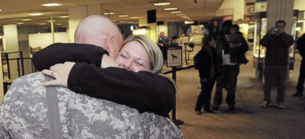 Sgt. Major Scott Doyon gets a hug from his wife Sara after his plane landed at Bangor International Airport on Sunday, November 21, 2010. Doyon is part of the Brewer-based Bravo Co. 3rd Battalion of the 172nd Mountain Infantry and was returning from deployment in Afghanistan. (Bangor Daily News/Kevin Bennett)