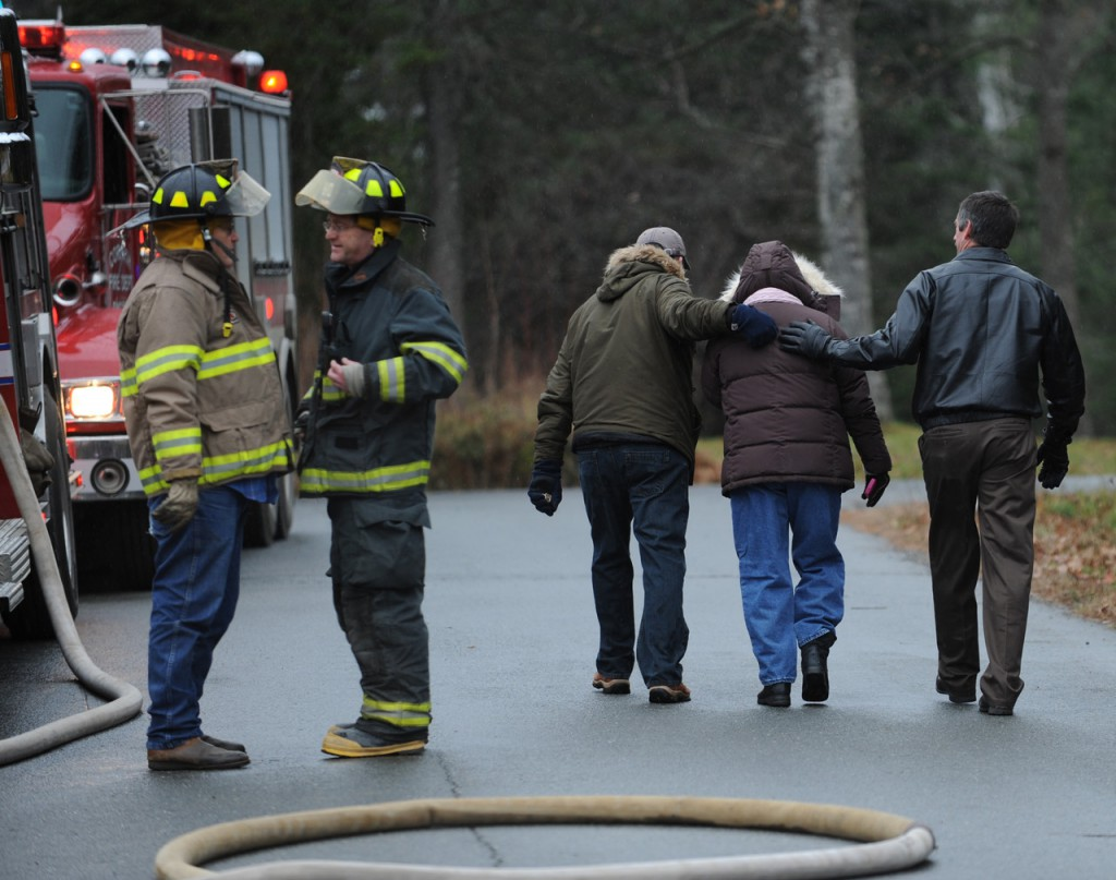 Two men comfort a woman at the scene of a house fire on Deer Run Road in Glenburn on Monday morning, November 22, 2010 as firemen talk next to their trucks. (Bangor Daily News/Kevin Bennett)