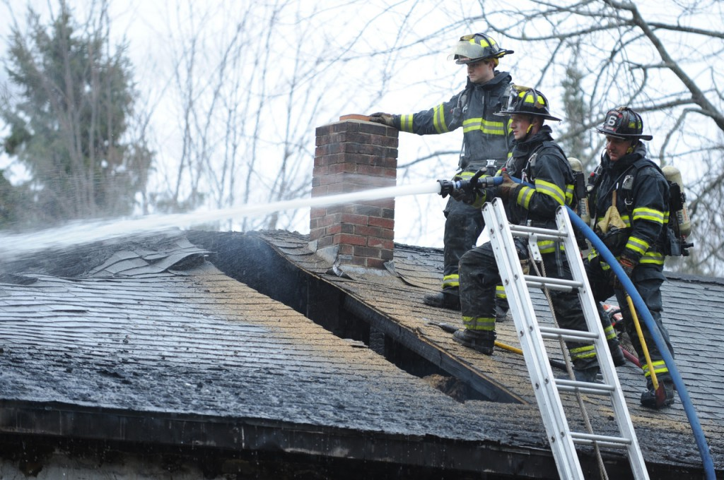 Firefighters from Bangor's Engine 6 (left to right) Ryan Blanchette, Chandler Corriveau and Kip O'Brien hose down a section of roof after cutting a hole while they battle a house fire on Deer Run Road in Glenburn on Monday morning, November 22, 2010. (Bangor Daily News/Kevin Bennett)