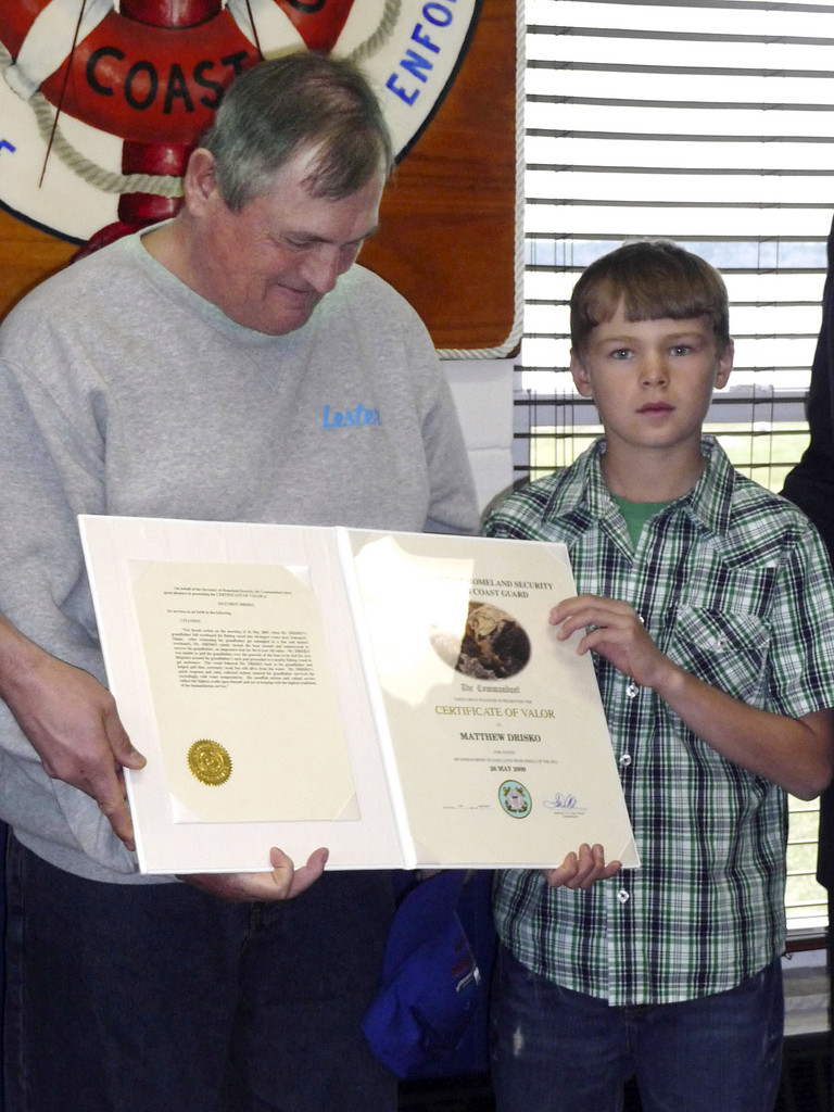Matthew Drisko, 9, of Addison, received the Dept. of Homeland Security's highest honor for civilians Monday, the Certificate of Valor, at a ceremony at the Jonesport station of the Coast Guard. In May of 2009, Matthew Drisko saved his grandfather, Lester Drisko, 55, of Addison (left), from drowning after the man fell overboard into 44-degree seas while lobster fishing of Beals Island. Matthew put his own life vest around his grandfather's neck and then piloted the lobster boat to nearby fishing vessel seeking help. U.S. Representative Michael Michaud was on hand for the presentation. BANGOR DAILY NEWS PHOTO BY SHARON KILEY MACK