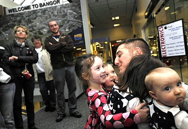 At Bangor International Airport Monday, Staff Sgt. Nicholas Theriault of Lewiston crouched for a group hug with his excited nephews and nieces as he and 15 other soldiers with Bravo Company, 3rd Battalion-172nd Mountain Infantry unit returned from their year-long deployment in Afghanistan. Hugging him (left to right) were Anna Theriault, 4, Gerek Potvin (cq), 4, Loreesa Potvin (cq), 5, and Molly Potvin, nine months--all of Lewiston. (Bangor Daily News/John Clarke Russ)