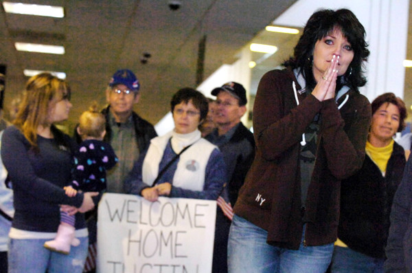 At Bangor International Airport Monday, Pam Collins of Canaan waits anxiously for the first sight of her son , Sgt. Nike Whitmore (cq) of Oakland, as he and 15 other soldiers with Bravo Company, 3rd Battalion-172nd Mountain Infantry unit returned from their year-long deployment in Afghanistan. Among those behind her was the family of Spc. Justin Harvey of Lincoln. Spc. Harvey's mother, Beth Harvey,  was holding the welcome sign. (Bangor Daily News/John Clarke Russ)