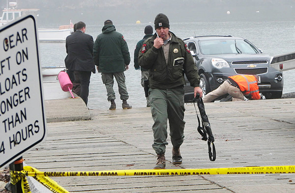 Maine Marine Patrol Specialist Colin MacDonald talked on his cell phone as he  walked away from the late model vehicle (in background) that was pulled from the water at  Seal Cove in Tremont late Tuesday morning. The bodies of 92-year-old Lewis Lawton and his 86-year-old wife, Inez, had been removed from the vehicle before this photo was taken. The submerged vehicle was sighted near the boat landing there around 7:30 am Tuesday. (Bangor Daily News/Bill Trotter)