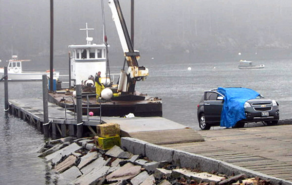 A late model Chevrolet Equinox, covered with a tarp, was pulled from the water at  Seal Cove in Tremont late Tuesday morning. On the left is the barge that helped remove it from approximately 13 feet of water about 30 yards off the boat landing. The bodies of  92-year-old Lewis Lawton and his 86-year-old wife, Inez,  were removed from the vehicle after this photo was taken. The submerged vehicle was sighted near the boat landing there around 7:30 am Tuesday. (Bangor Daily News/Bill Trotter)