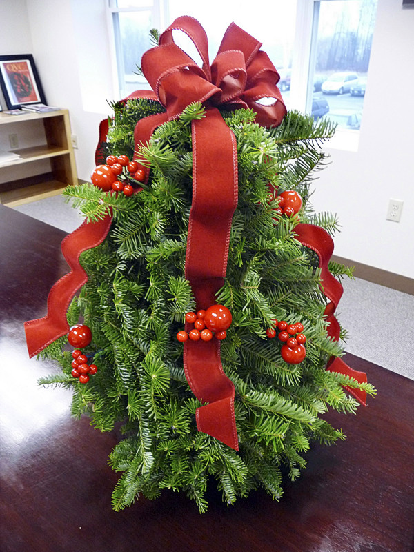 This tabletop tree, constructed at Whitney Originals in Whitneyville, is at the center of a lawsuit against the company filed by Worcester Wreath Company of Harrington. Company owner Morrill Worcester claims the tree violates a patented tree that Worcester creates. Whitney's tree is balsam tips decorated with red cascading ribbon and bright red berry clusters. It sells for $64.95 in the L.L. Bean holiday catalog. Worcester has 11 different tabletop trees on his company's website, www.worcesterwreath.com. All of them are decorated with pine cones, which Whitney's tree does not have. Some of Worcester's trees are also decorated with lights, cinnamon sticks, candy canes or cardinals. Worcester filed his suit Monday in U.S. District Court in Bangor. BANGOR DAILY NEWS PHOTO BY SHARON KILEY MACK