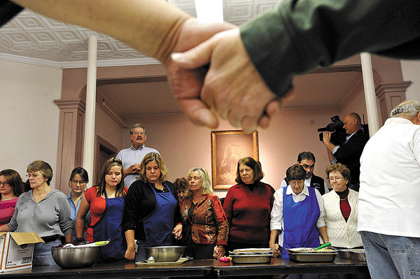 Community members, joining hands, bowed their heads as Manna Minstries executive director Bill Rae, upper left, led a prayer of  before the start of Manna Ministries annual free Thanksgiving dinner at Columbia Street Baptist Church in Bangor Thursday morning. Over 100 volunteers and over 100 other area residents attended the event which included approximately 70 pumpkin pies and 30 turkeys-- thanks in large part to area donations. (Bangor Daily News/John Clarke Russ)