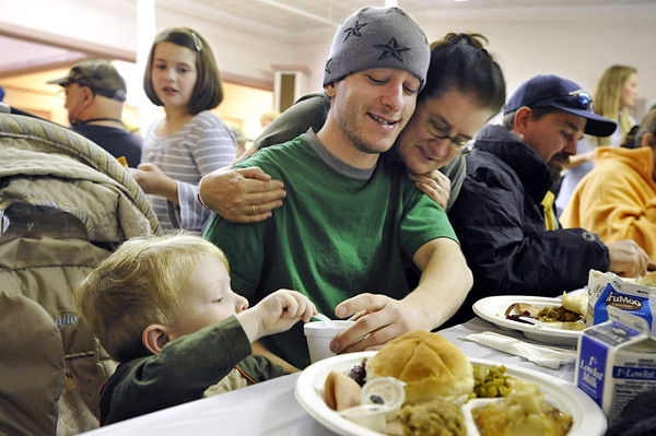 Volunteer Tina Jackacky of Glenburn hugged Chris Bryden of Bangor as he and his two-year-old son Noah, left,  enjoyed their meal during Manna Ministries annual free Thanksgiving dinner at Columbia Street Baptist Church in Bangor Thursday morning. Walking by  with a slice of pumpkin pie was volunteer Morgan Lagasse upper left, 8,  of Bangor.  Over 100 volunteers and over 100 other area residents attended the event which included approximately 70 pumpkin pies and 30 turkeys-- thanks in large part to area donations. (Bangor Daily News/John Clarke Russ)