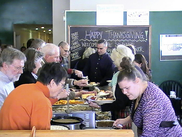 Members of the greater Ellsworth community form a line at lunchtime Thursday during the second annual community dinner hosted by the Emmaus Center and the Riverside Cafe. All the food was donated and offered to patrons free of charge.   BANGOR DAILY NEWS PHOTO BY ERIC RUSSELL  3 col max