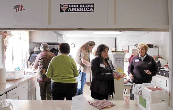 ORRINGTON, ME -- NOVEMBER 25, 2010 -- The ladies gather the food in the kitchen of the church to set up the buffet table for dinner to start. LINDA COAN O'KRESIK