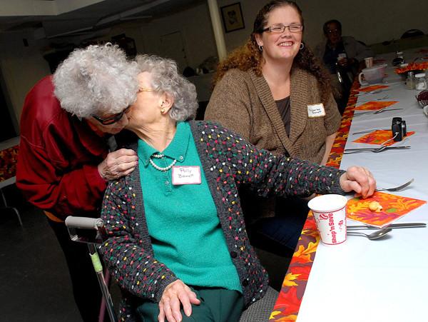 ORRINGTON, ME -- NOVEMBER 25, 2010 -- Polly Smith Bennett, 92, kisses her sister Louise Smith Perkins, 87, when she arrives at the Smith family Thanksgiving. Four generations of the Smith family gather annually at the First United Methodist Church in Orrington.  Sitting with Polly is her grand daughter Kimberlee Bennett. LINDA COAN O'KRESIK