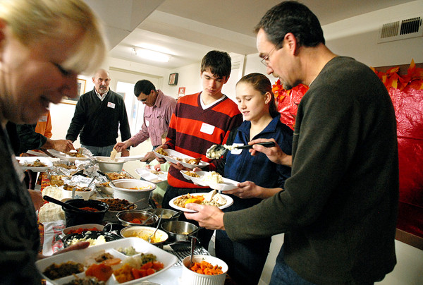 ORRINGTON, ME -- NOVEMBER 25, 2010 -- Dan Caron, his daughter Shelby, 13, and nephew Zach, 18, fix dinner plates at their family Thanksgiving celebration at the First United Methodist Church in Orrington. LINDA COAN O'KRESIK