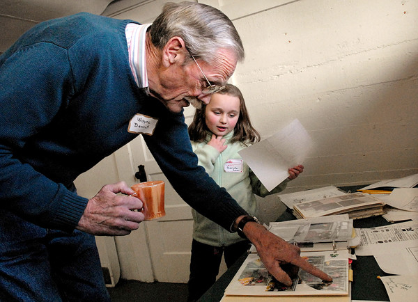 ORRINGTON, ME -- NOVEMBER 25, 2010 -- Wayne Bennett shows his great niece Charlotte Caron, 6, photos from past Thanksgiving feasts.  Charlotte is the youngest in the Smith family tree. LINDA COAN O'KRESIK