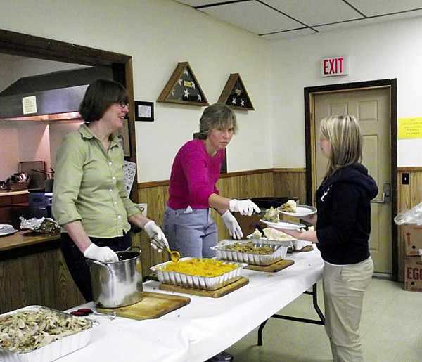 TURKEY IN FORT, CUT LINE, FORT FAIRFIELD -- Barbara Hayslett, far right (in  pink,) spoons some stuffing onto the plate of a volunteer server waiting to  deliver it to the table of a hungry diner during the annual Community Thanksgiving Dinner at the Fort Fairfield VFW Hall on Thursday, Nov, 25, 2010. More than 80 people came to Fort Fairfield VFW hall for the feast, which was organized by the Fort Fairfield Knights of Columbus, the VFW and the Fort Fairfield Rotary Club. Volunteers also delivered an estimated 100 meals to people who could not make it to the dining hall. (BANGOR DAILY NEWS PHOTO BY JEN LYNDS)