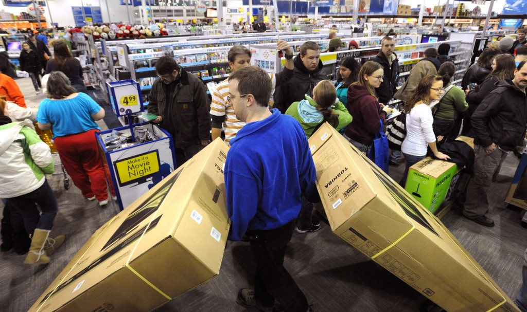 Kenn Kelley and enventory specialist at the Best Buy in Bangor navigates through the customer-filled store with two 55&quot LCD televisions so the new owners can pick them up at the cash register.  The store opened at 5am Friday with hundreds of people standing in line to take advantage of the discounts. (Bangor Daily News/Gabor Degre)