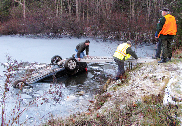 Morrill Fire Chief Pat Scribner crawls across a ladder Friday afternoon to attach a cable to the partially-submerged car that had flipped into a pond off Poland Woods Road. The driver, 20-year-old Jacob Mehuren of Brooks, was able to squeeze out a broken window and suffered only mild hypothermia. (Abigail Curtis/ BDN)