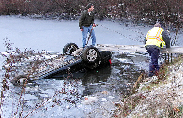 Morrill Fire Chief Pat Scribner stands atop a partially-submerged car Friday afternoon as rescue crews worked to get it out of a pond on the Poland Woods Road. (Bangor Daily News/Abigail Curtis)