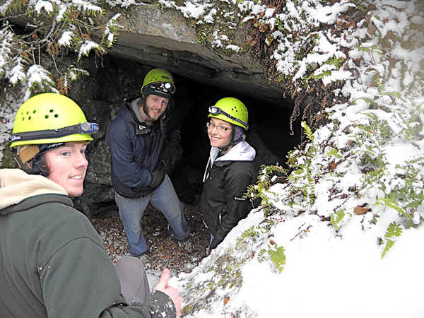 University of Maine at Presque Isle students Gordie Scannell, Adam Dunn and Courtney Cray take a break before entering a Quebec cave during last weekend's OAPI outing. (Photo by Julia Bayly).