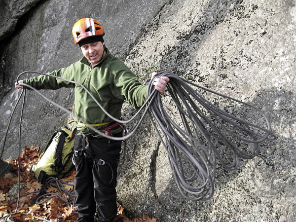 Teirney coils the climbing rope he will use for the ascent of the wall to his left. Parks Pond Bluff is a popular climbing spot in Clifton where Tierney has established many first ascents of difficult technical climbing routes.