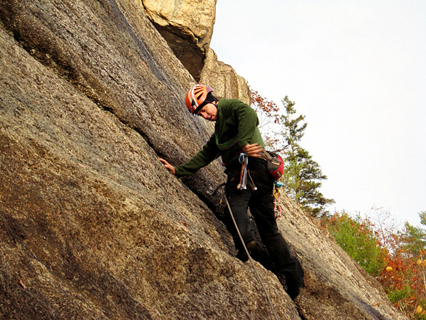 Tierney reaches for a piece of climbing equipment to place in the crack in the rock on the ascent of Parks Pond Bluff in Clifton.