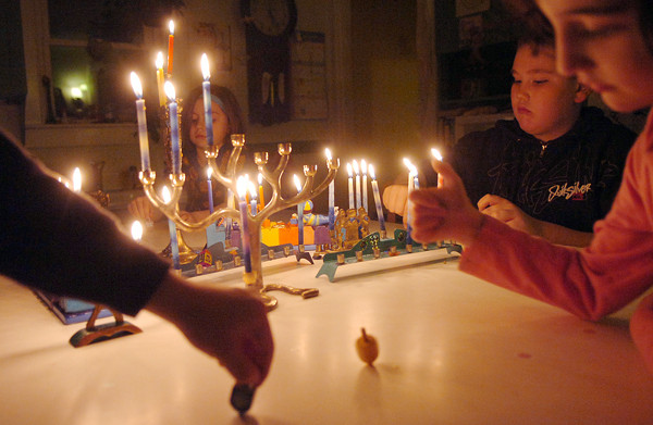 Rosie-Cobo-Lewis (right) and Zachary Welch-Lewis (second from right) spin dreidels after lighting numerous menorahs in celebration of the third night of Hanukkah. The two were among a group of children and adults who gathered in the Orono home of Lori Osher for her annual Hanukkah party.  (BANGOR DAILY NEWS PHOTO BY KATE COLLINS)