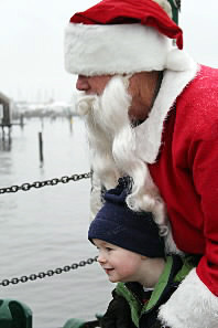 Brady Harrington, 3, of Hanover, Mass. got a hug from Santa on the Rockland Public Landing Friday morning at the kickoff to the city's Festival of Lights, which runs through Sunday. (Bangor Daily News/Heather Steeves)