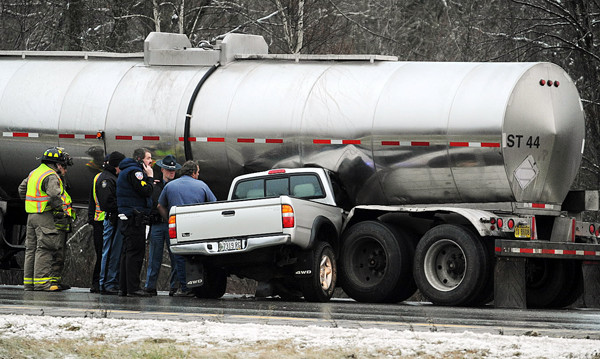 Fire and police personnel inspect the damage to both a tanker truck and small pick up truck driven by Kelsey Devine of Bangor. Devine skidded on slick pavement on Friday as she was driving northbound on I-95 in Hampden, bounced off a guardrail and embedded her truck under the wheels of a tanker truck loaded with paper mill waste from Macon Georgia.  Maine State Trooper Michael Johnston said the tanker driver, Steven Pennington of Georgia, then dragged Devine and her truck about a quarter mile before bringing the tanker to a stop. Devine received only minor cuts and scrapes.   BANGOR DAILY NEWS PHOTO BY KEVIN BENNETT