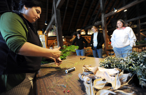 Patricia Henner instructs a group of people on the proper way to create a decorative wreath made of items common to most peoples yard at the Page Farm and Home Museum on the campus of the University of Maine on Saturday, November 27, 2010. (Bangor Daily News/Kevin Bennett)