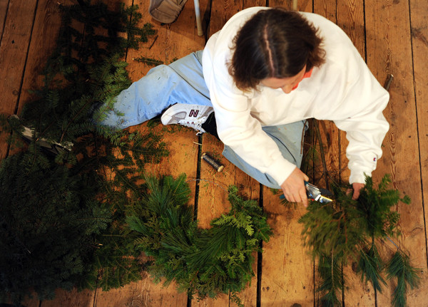 Linda Hoar of Guilford sits on the floor of the Page Farm and Home Museum on Saturday, November 27, 2010 as she makes a decorative wreath of balsam during a wreath making workshop. Hoar who grew up in Virginia says she used to make wreaths as a child from items found in her backyard. This is her first workshop making a wreath with guidance. (Bangor Daily News/Kevin Bennett)
