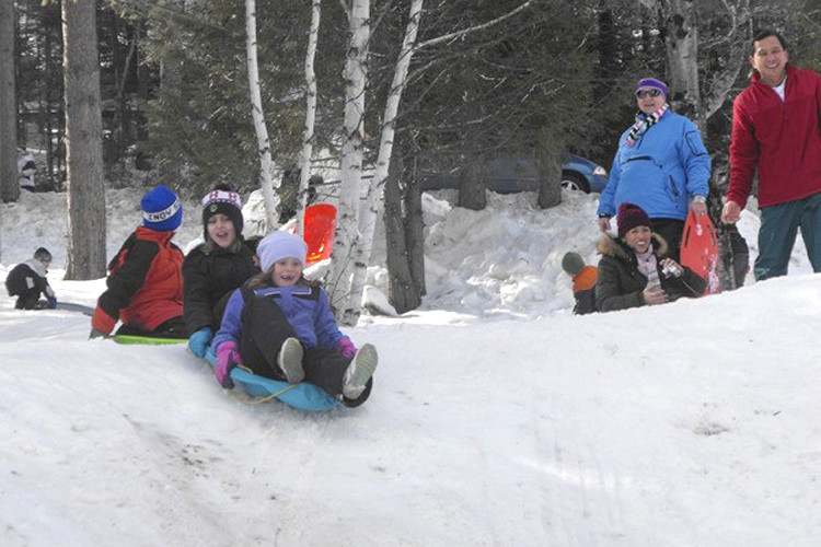 Children and adults enjoyed the sliding hill at Aroostook State Park during the third annual Take It Outside Winter Family Fun Day in February. Participants brought their own sleds or toboggans for a fast 200-yard run down the hill out onto Echo Lake. Hundreds of people came to the Presque Isle park on Saturday to ski, showshoe, ice skate, take dog sled rides and more. (BDN/Jen Lynds)