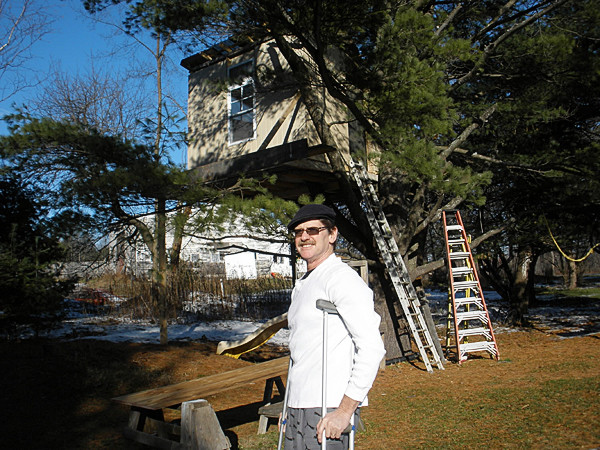 News photo by Joni Averill   Tim Higgins stands before the tree house he was building for his children before he fell and crushed his ankle and broke a rotator cuff, both of which will require extensive surgery that will keep him out of work for some time.
